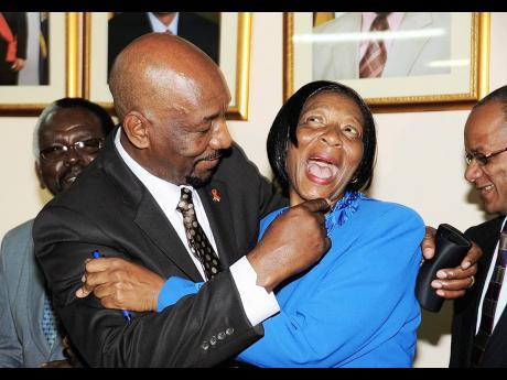 Edith Allwood-Anderson enjoys a playful moment with then Health Minister Rudyard Spencer after signing a wage agreement in September 2009.