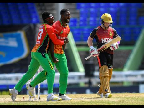 Romario Shepherd (centre) and Kevin Sinclair (left) of Guyana Amazon Warriors celebrate winning against the Trinbago Knight Riders in the super over during the 2021 Hero Caribbean Premier League cricket match at Warner Park Sporting Complex in Basseterre,
