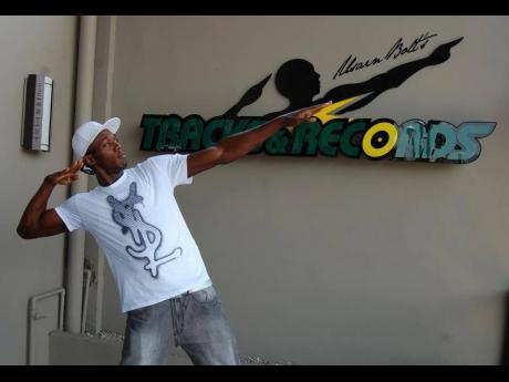 Usain Bolt poses in front of the Usain Bolt Tracks & Records sign in this 2013 file photo.