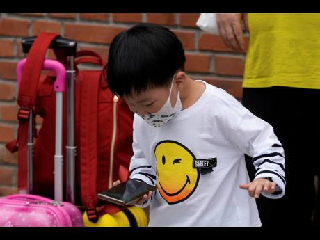AP A child wearing a face mask plays game on a smartphone next to his relative in Beijing Sept. 12, 2021.