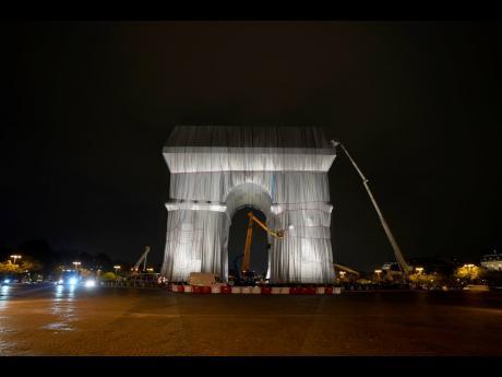 Workers wrap the Arc de Triomphe monument.