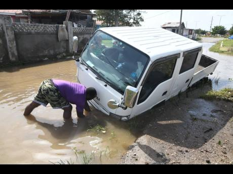 A resident of Callaloo Mews, St Andrew, affixes a chain to a disabled pickup van on a flooded road in the community after the passage of Tropical Storm Grace.