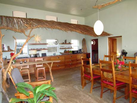 An unexpected fig-wood canopy  (below the main ceiling) defines the kitchen area.