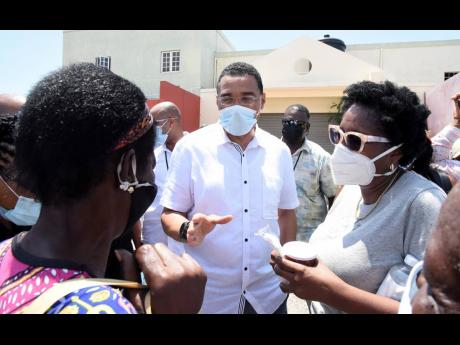 Prime Minister Andrew Holness (centre) and St Andrew South Western Member of Parliament Dr Angela Brown-Burke (right) speaking with residents of the constituency during a vaccine mobilization and public education campaign on Friday.