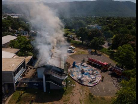 Firefighters working to extinguish a blaze at a painting studio at the Edna Manley College of the Visual and Performing Arts in Kingston yesterday. The probe into the cause of the fire and an assessment of the damage could take a month, officials have said