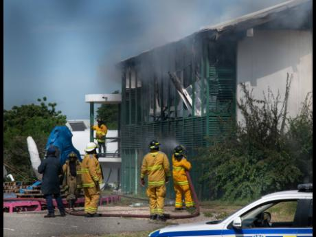 Firefighters conduct cooling-down exercises on a building which was razed by fire at the Edna Manley College of the Visual and Performing Arts in Kingston on Friday.