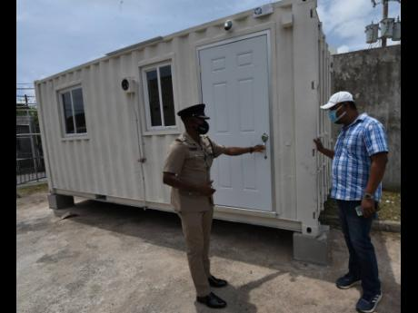 Superintendent Christopher Phillips (left), who is in charge of the 100 Man Police Station in Greater Portmore, St Catherine, and Charroc Construction contractor Raymond Green examine a container that was delivered to the station to be used as an office fo