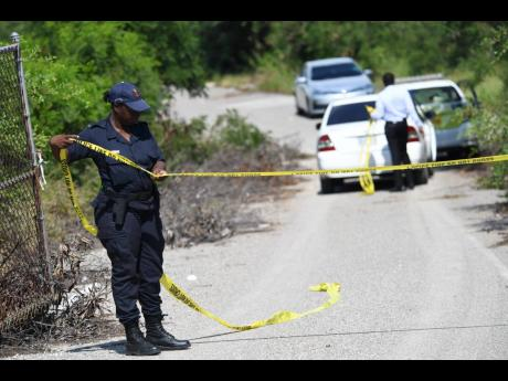 A policewoman cordons off the entrance to the now-defunct fishing village off the Portmore toll road in St Catherine, where the body of a woman was discovered in November 2019.