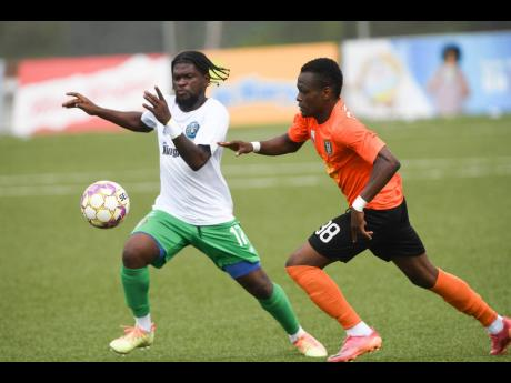 Vere United's Ricardo Dennis (left) dribbles away from Tivoli Gardens' Romaine Bowers during a Jamaica Premier League first leg quarter-final match at the UWI-JFF-Captain Horace Burrell Centre of Excellence yesterday. The match ended 0-0.