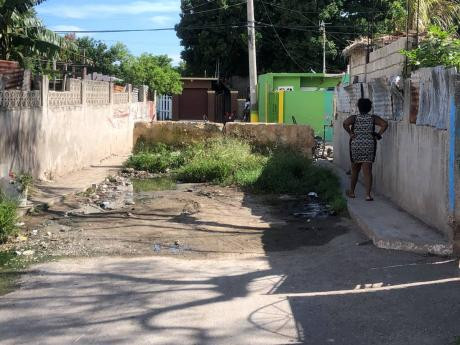 A woman walks past a blockade at the intersection of Stevens Lane and Bowens Road in Kingston. Greater Kingston is a bubbling pot of turf wars that place persons living on borderlines at risk of death and injury from rival gangs.