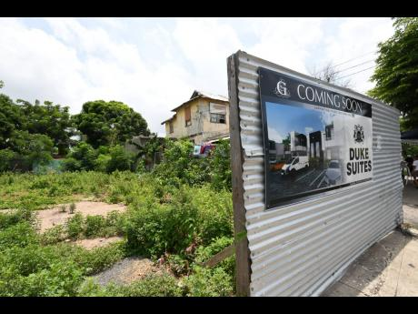 Undeveloped land on Duke Street, Kingston, forms the backdrop for a sign of the imminent Duke Suites complex being undertaken by Global Designs and Builders Ltd.