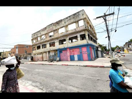 Two women walk past a decaying building on Tower Street in downtown Kingston.
