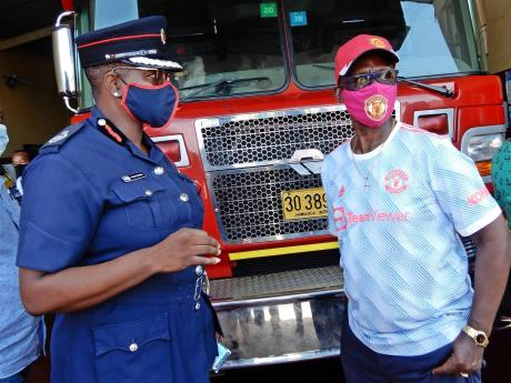 Minister of Local Government and Community Development, Desmond McKenzie (right) and Assistant Commissioner of the Jamaica Fire Brigade, Julian Davis-Buckle, in discussion at the Ocho Rios fire station Friday afternoon.