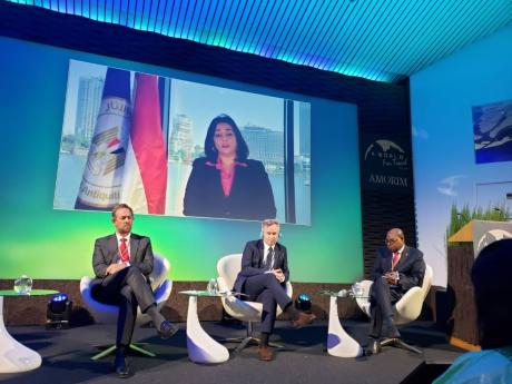 Tourism Minister Edmund Bartlett (right), listens attentively to the points raised by Ghada Shalaby, vice minister, tourism and antiquities, Arab Republic of Egypt (on screen) during a panel discussion at the highly anticipated 'A World for Travel – É