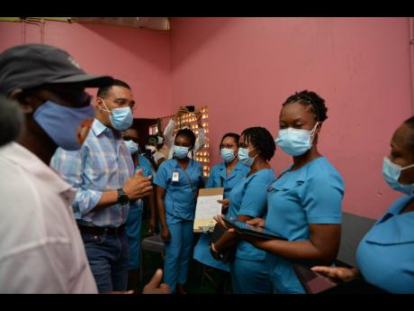 Prime Minister Andrew Holness (second left), gives words of gratitude and encouragement to healthcare workers at the vaccine site at Cross Keys High School during his tour of blitz sites in Manchester on September 16.