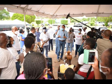 Prime Minister Andrew Holness (centre), addresses residents gathered at the Cross Keys High School to receive their COVID-19 vaccine during his tour of blitz sites in Manchester on September 16. He was accompanied by Local Government and Rural Development