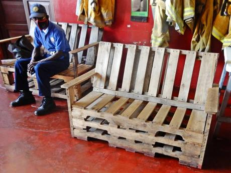 A firefighter at the Ocho Rios fire station sit on one of several benches that firefighters at the station made, in the absence of sufficient seating at the fire station. Local Government Minister Desmond McKenzie has instructed that new chairs be ordered