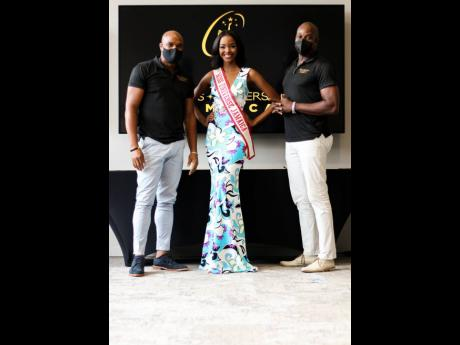 Reigning Miss Universe Jamaica Miqueal-Symone Williams stands in-between co-national directors Karl Williams (left) and Mark McDermoth as she gets ready to announce the names of the applicants who will advance to the next leg of the pageant.