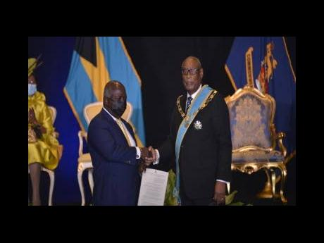 Prime Minister Philip Davis (left), receives his instruments of appointment from Governor General Sir Cornelius Smith on Saturday.