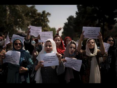 Afghan women march to demand their rights under the Taliban rule during a demonstration near the former Women's Affairs Ministry building in Kabul, Afghanistan yesterday.