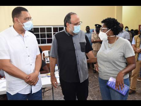 Prime Minister Andrew Holness looks on as Mark Golding (centre), opposition leader, is greeted by Dr Angela Brown Burke, member of parliament for St Andrew South Western, at a vaccination mobilisation and public education campaign on Friday.