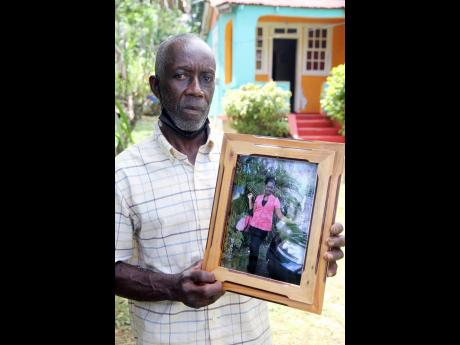 Ean Richards displays a photograph of his daughter Annakaye Richards, 32. The mother of two was murdered at home in Comfort, Manchester, Friday evening.