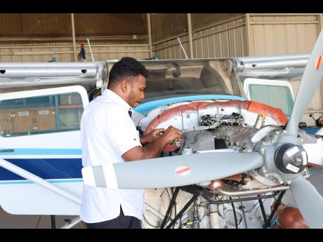 Maintenance Director at the Aeronautical School of the West Indies Christopher Gooding, works on the Aeronautical School of the West Indies (ASWI) training aircraft at the Tinson Pen Aerodrome. Gooding turned his love for flying into a business opportunity