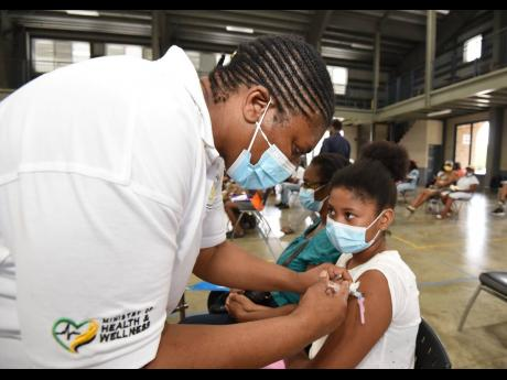 Public health nurse Pauline Simpson administers a dose of Pfizer to Lee-Anne Oakley during a vaccination blitz held at Jamaica College on Monday, August 23. Children aged 12 and over are eligible for the COVID-19 vaccine.