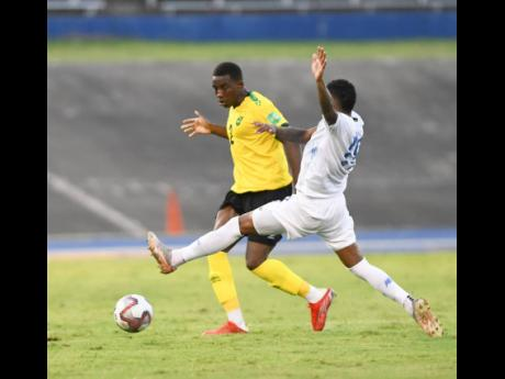 Jamaica's Wesley Harding (left) plays the ball while under pressure from Panama's Alberto Quintero Medina during a World Cup qualifying football match at the National Stadium in Kingston on Sunday, September 5.