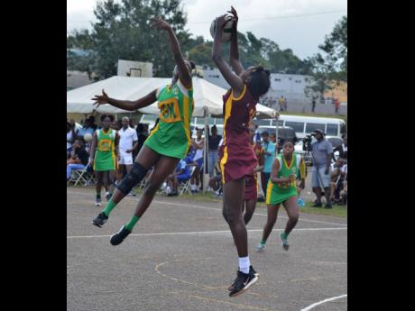 Holmwood High School goal-attack Alliah Lue (right) catches a ball ahead of Patrice Ranking during the ISSA All-Island Netball Final held at the Manchester High School court in Mandeville, Manchester on Wednesday, December 11, 2019.