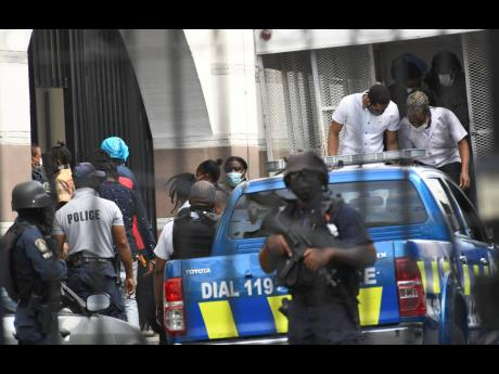 Some of the alleged 33 members of the One Don-Clansman Gang alight from a truck before entering the Home Circuit Court in downtown Kingston on Monday.