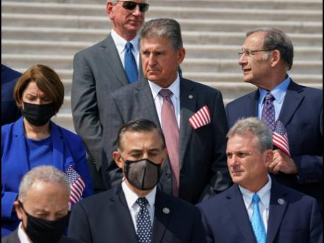 Sen Joe Manchin, D-W.Va., stands beside Sen Amy Klobuchar, D-Minn., left, and other lawmakers on the steps of the Capitol during a Sept 11 remembrance ceremony, in Washington, Monday, Sept 13, 2021. As congressional Democrats speed ahead this week in pursu