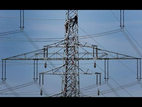 Workers of the German energy company RWE prepare power supply on a high power pylon in Moers, Germany.