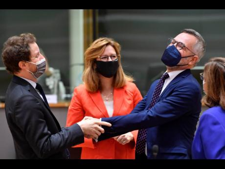 Germany's European Affairs Minister Michael Roth (second right) greets French counterpart Clement Beaune (left), during a meeting of EU General Affairs ministers at the European Council building in Brussels yesterday.