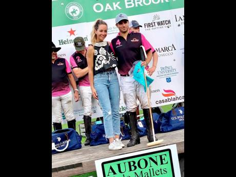 Santi Torres (right) won the Most Valuable Player Award following the match last Sunday. He is joined in the presentation by polo player Pamela Flanagan.
