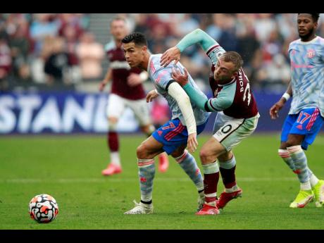 Manchester United's Cristiano Ronaldo (left) is held by West Ham's Jarrod Bowen during the English Premier League match at the London Stadium in England on Sunday, September 19. United won 2-1. Both teams meet again in League Cup action today.