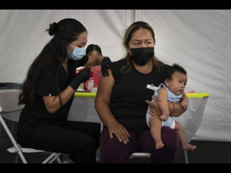 Laura Sanchez (right) holds her two-month-old son, Lizandro, while receiving the Pfizer COVID-19 vaccine from Registered Nurse Noleen Nobleza at a vaccine clinic set up in the parking lot of CalOptima in Orange, California.