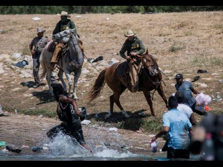 US Customs and Border Protection mounted officers attempt to contain migrants as they cross the Rio Grande from Ciudad Acuña, Mexico, into Del Rio, Texas, on Sunday.
