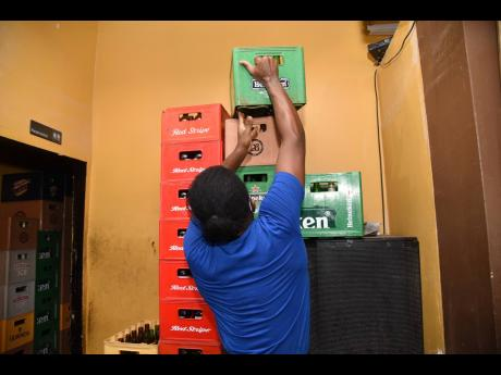 Anthony Easy packs crates of empty bottles in a corner at Beer Grillz Bar and Restaurant, located in Port Henderson Plaza.