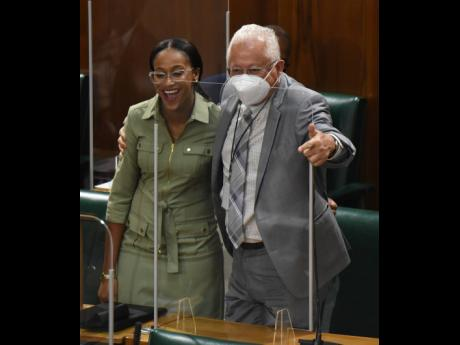 Rhoda Crawford (left), member of parliament for Manchester Central, gets a congratulatory hug from Delroy Chuck (right), member of parliament for St Andrew North East, shortly after she made her debut presentation to the state of the constituency debate in