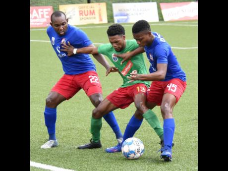 Mark Rodney (centre) from Humble Lion tries to shield the ball from Dunbeholden players Rondee Smith (left) and Graig Gayle during a Jamaica Premier League match on Friday, August 27, 2021.