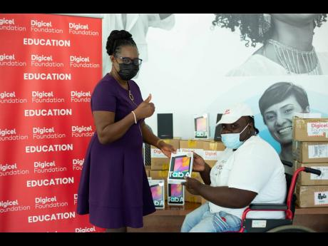 Digicel Foundation donates an additional 100 tablets to students with special needs. Jeneard Williamson, education and special needs officer, Digicel Foundation, presents Dr Christine Hendricks, executive director of the Jamaica Council for Persons with Di