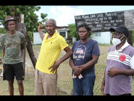 Carlton Campbell (second left), of Project Land Lease, Raymonds Clarendon explains the terms of a lease agreement signed in the 1970s between residents and then Minister of Agriculture Keble Munn, to lease over 700 acres of land to 220 farmers for 49 years