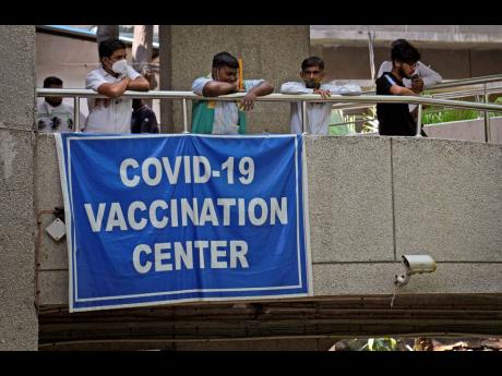 People watch others arrive to receive the COVID-19 vaccine at a government-run hospital in New Delhi, India, on Tuesday.