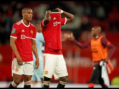 Manchester United's Anthony Martial (left) and Eric Bailly leave the pitch at the end of the English League Cup match against West Ham at Old Trafford in Manchester, England, yesterday.