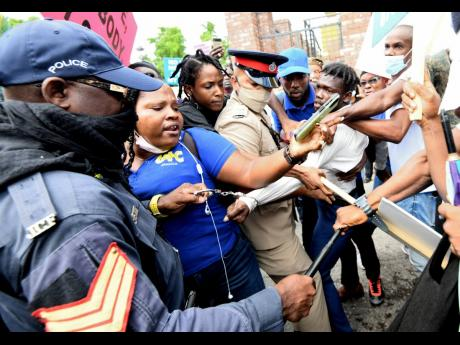 Fellow protesters try to stop the police from detaining this young man as they marched towards Gordon House in protest against what they believe is an impending move by the Government to make the COVID-19 jab mandatory.