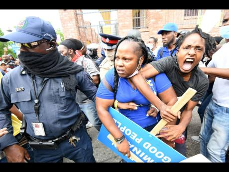 Police detain a protester during an unauthorised march in downtown Kingston yesterday.
