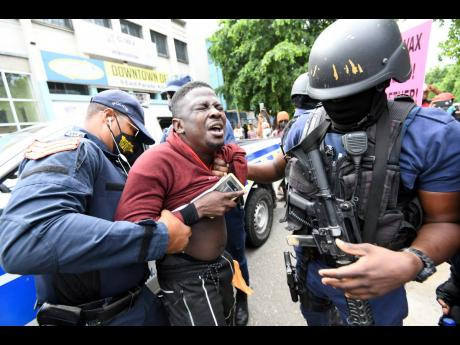 Police officers search one of the protesters before detaining him as they tried to break up an unauthorised march against COVID-19 vaccines in downtown Kingston yesterday.