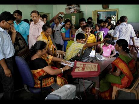 In this Wednesday, May 16, 2012 file photo, Indians crowd a room as they wait to enrol for Aadhar, India's unique identification project in Kolkata, India. A US-based private cybersecurity company said on Wednesday, September 22, it has uncovered evidence