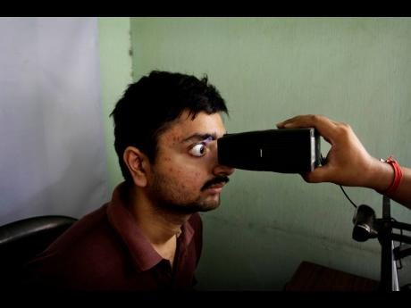 In this May 16, 2012 file photo, an Indian man gets his retina scanned to register for Aadhar, India's unique identification project, in Kolkata, India. A US-based private cybersecurity company said on Wednesday, September 22, it has uncovered evidence tha
